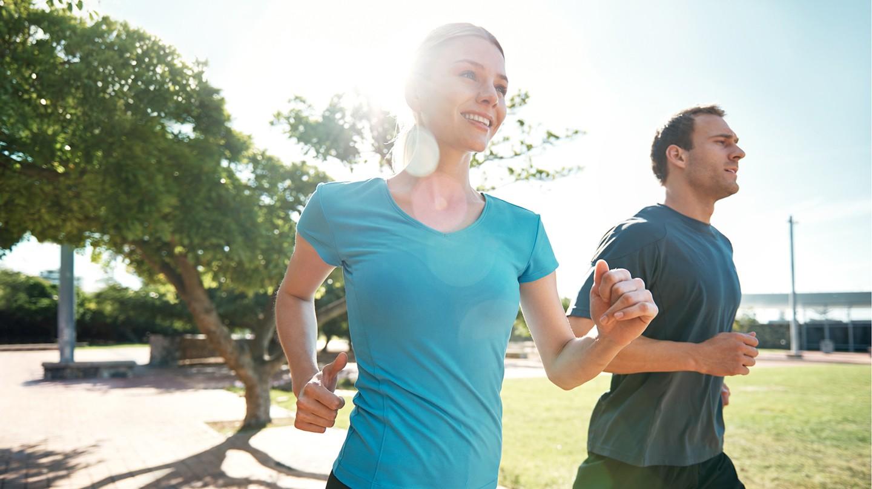 Ein Mann und eine Frau sind draußen und joggen durch einen Park.