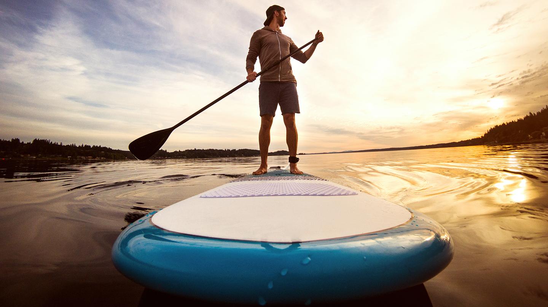 Rückenfreundliche Sportarten: Mann beim Stand-Up-Paddling auf einem See in der Abendsonne.