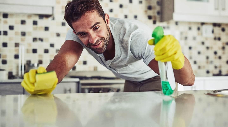 Zu viel Hygiene: Ein Mann mit Putzhandschuhen und Schwamm in der Hand besprüht in der Küche eine Arbeitsfläche mit Putzmittel.